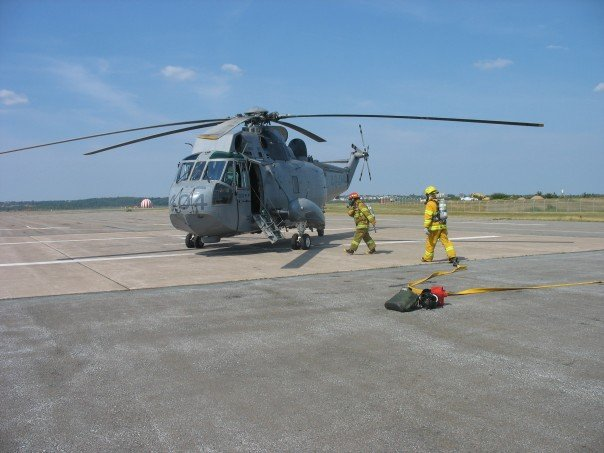 A CH-124 Sea King from 423 Maritime Helicopter Squadron, based at 12 Wing Shearwater, is inspected by firemen during a hot refuelling procedure. PHOTO: Officer Cadet Victor Weston