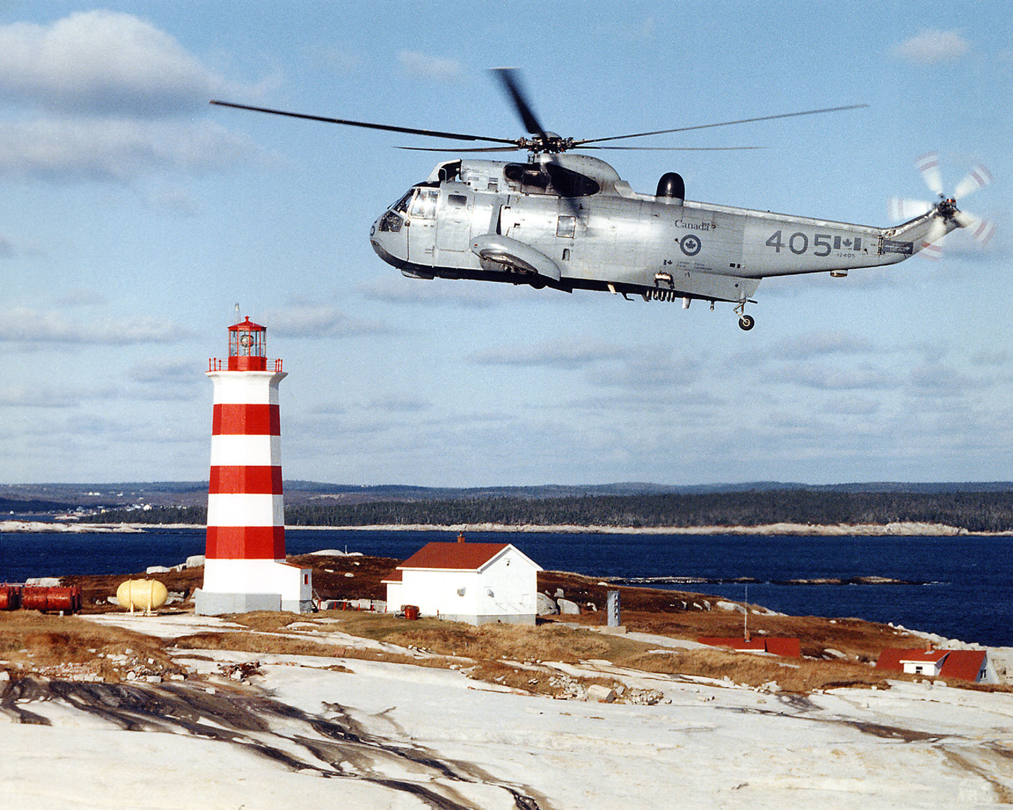 A CH-124 Sea King flies over a lighthouse in Nova Scotia. PHOTO: DND, negative SWC-85-2425-2