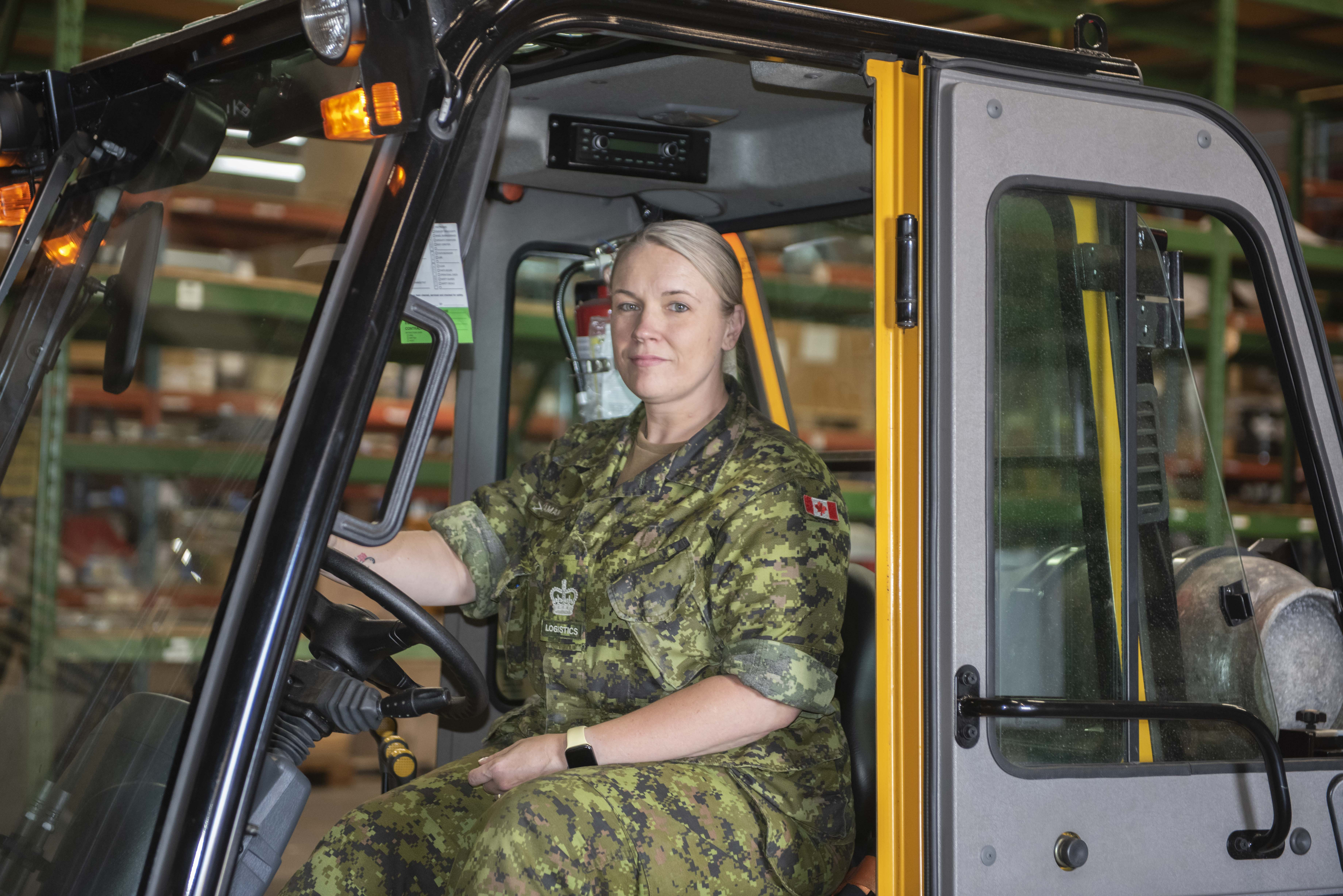 A woman wearing a camouflage uniform sits at the wheel of a vehicle.
