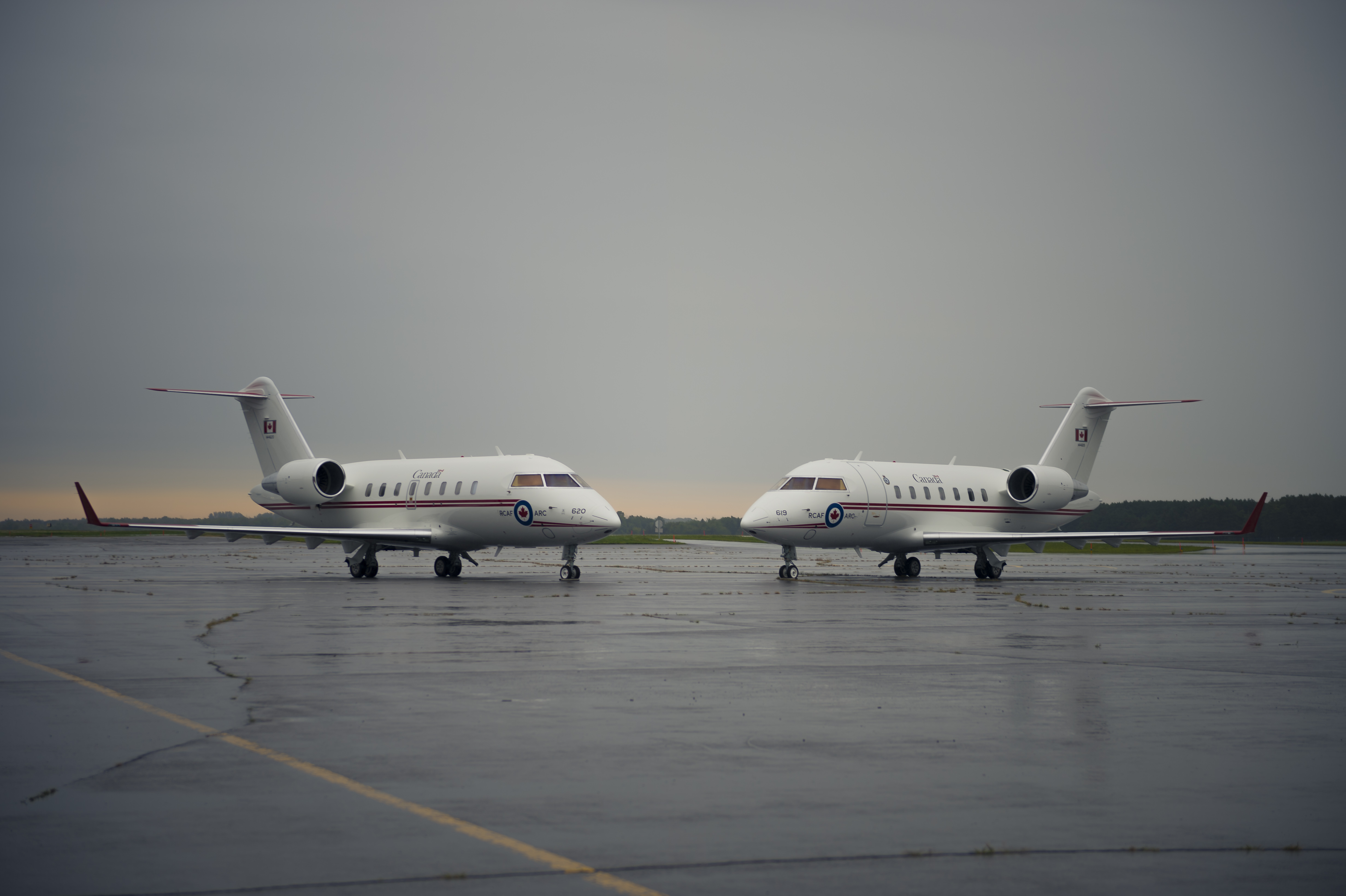 Two white medium-sized jet aircraft on a runway.