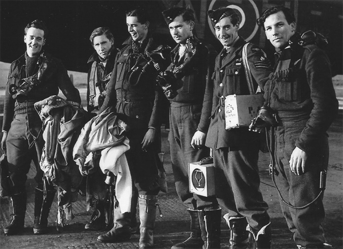"Flight Sergeant Lewis Burpee with members of his 106 Squadron Lancaster crew at RAF Syerston after a night operation on January 18, 1943. Those of his 106 Squadron crew who volunteered for a second tour stayed with him when he transferred to 617 Squadron: (from left) Gordon ""Gordie"" Brady, rear gunner; William ""Ginger"" Long, air gunner; and Guy ""Johnny"" Pegler, flight engineer. PHOTO: Via the Canadian Virtual War Memorial"