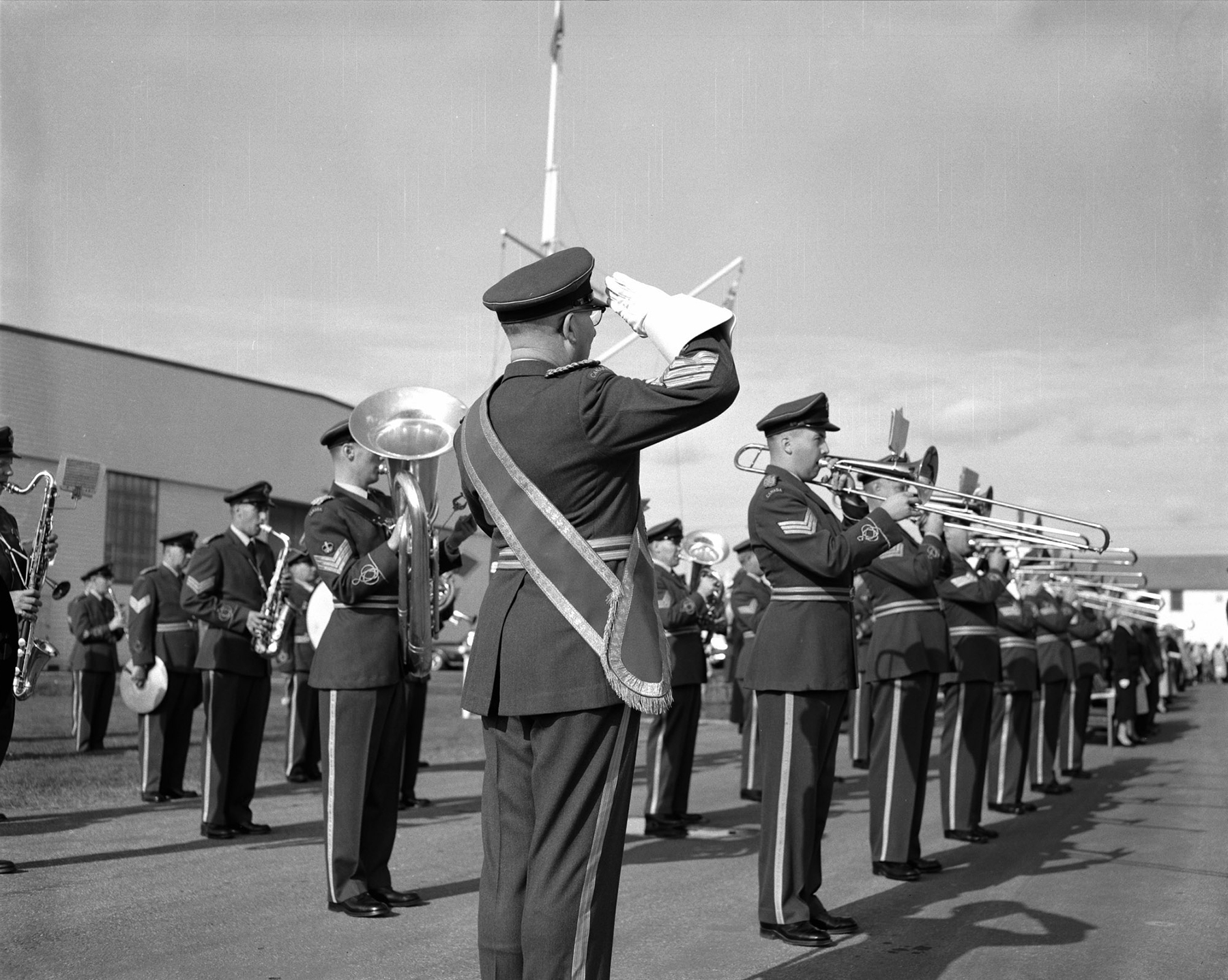"Warrant Officer second class J.C. Reid salutes as the Training Command Band plays ""Last Post"" and ""Rouse"" during the Battle of Britain Parade at RCAF Detachment Kingsway in Edmonton, Alberta, on September 20, 1959. PHOTO: DND Archives, PL-77424"