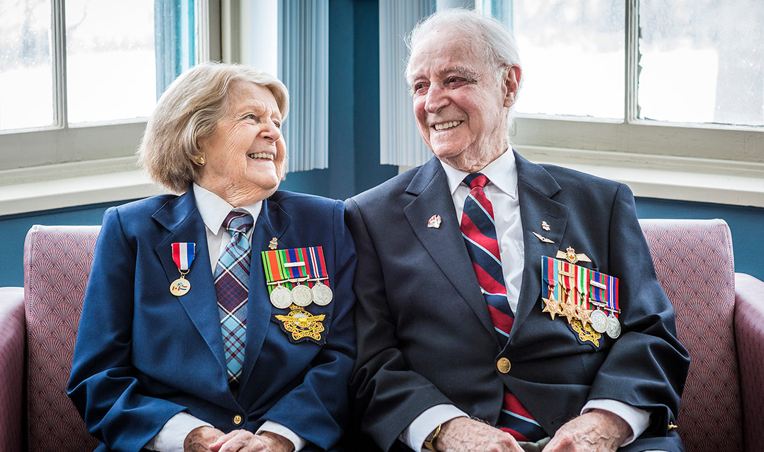An elderly woman and man wearing blazers with medals sit on a couch, looking at each other and smiling.