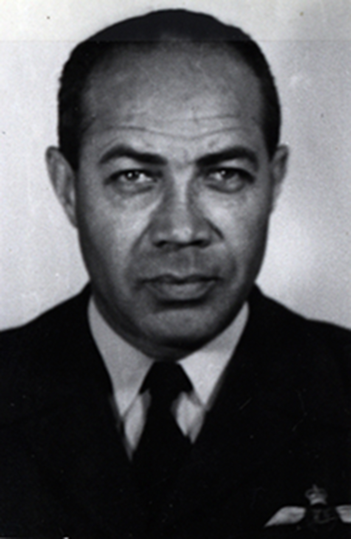 A black and white photo of a black man wearing a shirt and tie, and a uniform jacket with wings.
